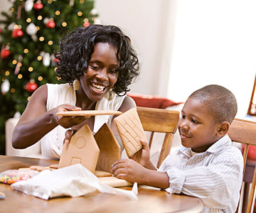 mother and son making gingerbread house