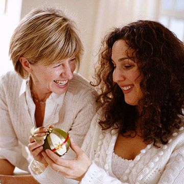 Two women with a Christmas tree ornament