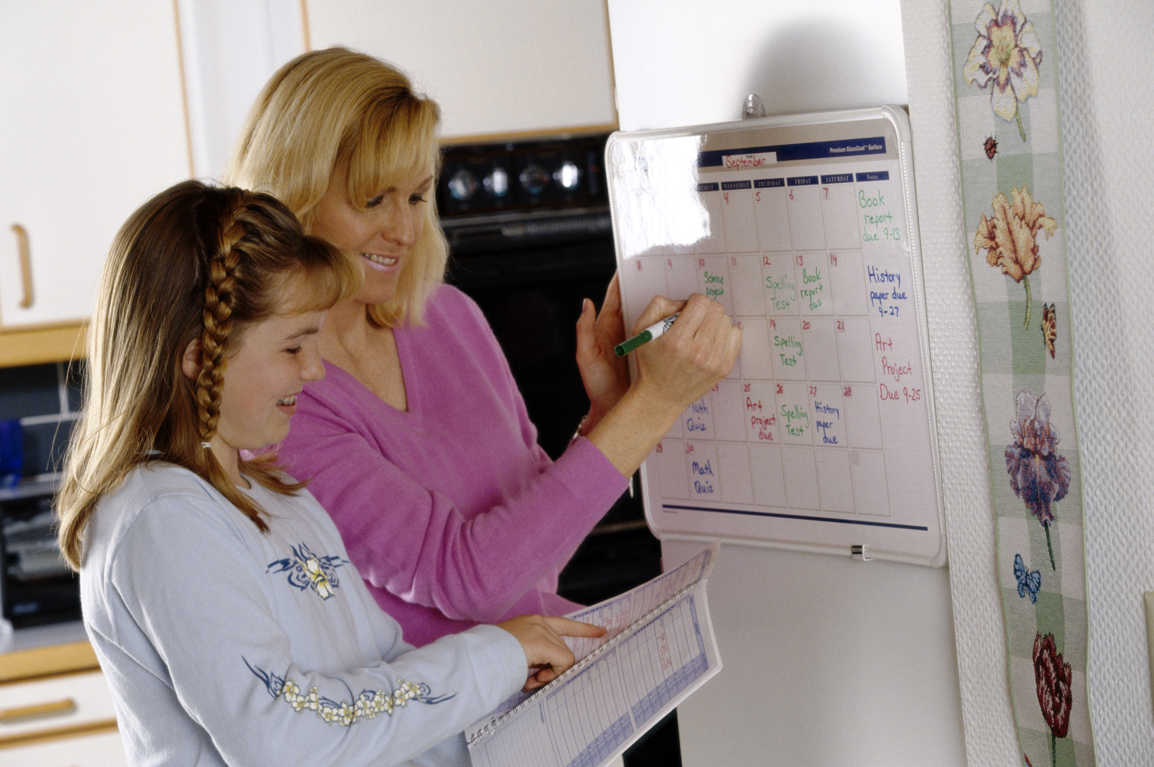Mom and daughter writing on calendar