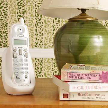 Phone on a table with a stack of pregnancy books next to it