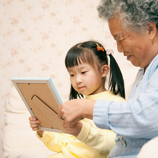 Grandmother showing granddaughter picture frame
