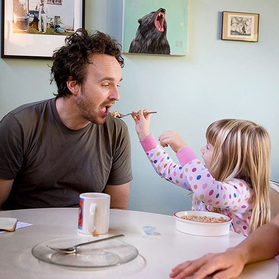 Girl feeding dad