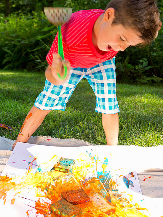 Boy with green-handled spatula over paint-splattered poster board and sponges