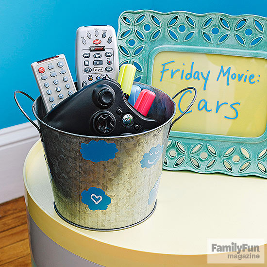 TV remotes in bucket in front of a picture frame