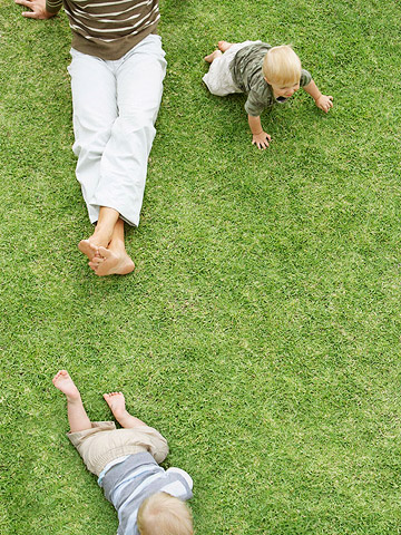 babies crawling outside in the grass
