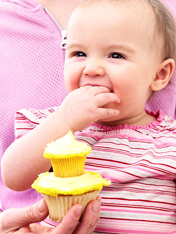 Baby girl eating a cupcake