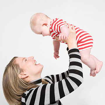 woman holding baby up in air