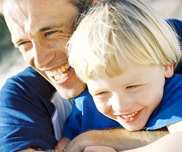Dad embracing blond son from behind, outside