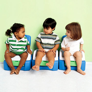 Three children sitting on potty chairs