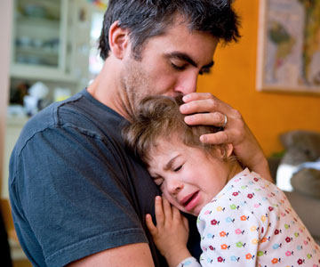father comforting crying child