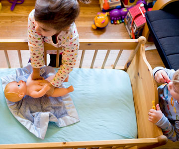 little girl putting baby doll in a crib