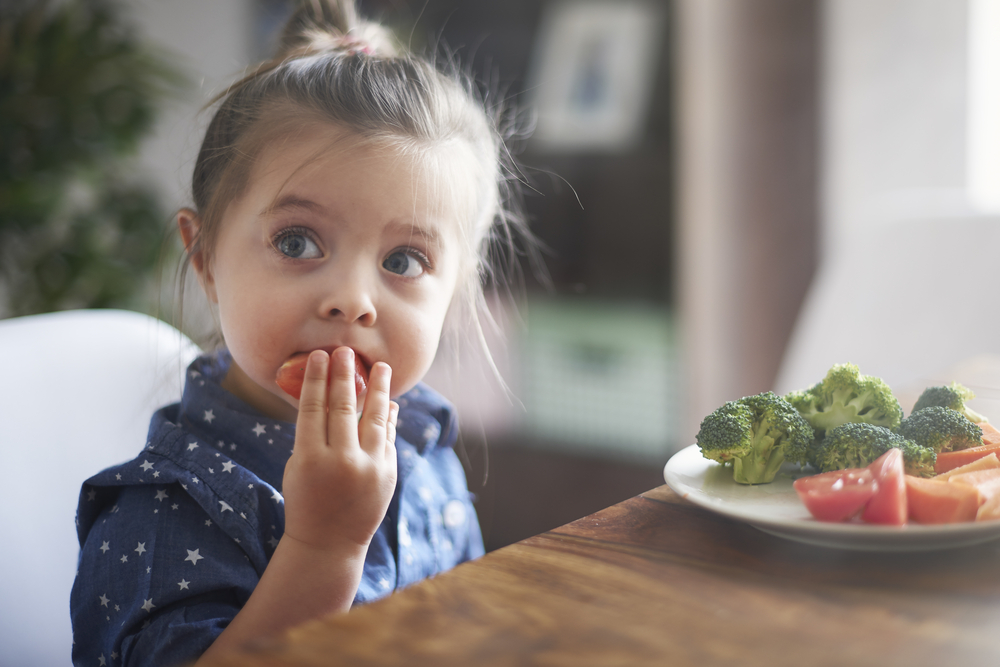 Young girl eating vegetables at table