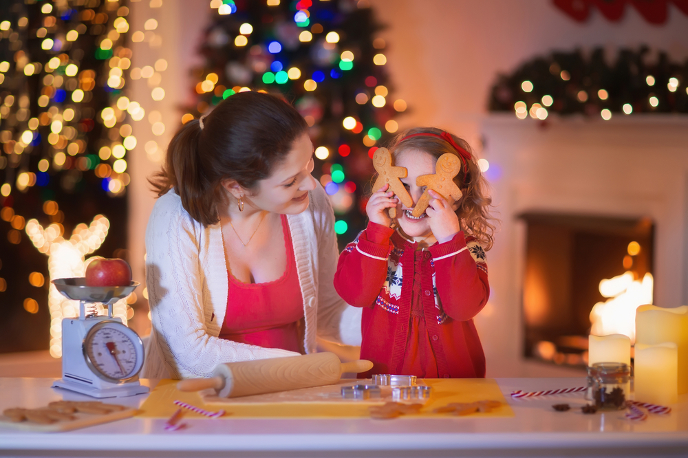 Girl making gingerbread cookies with mom