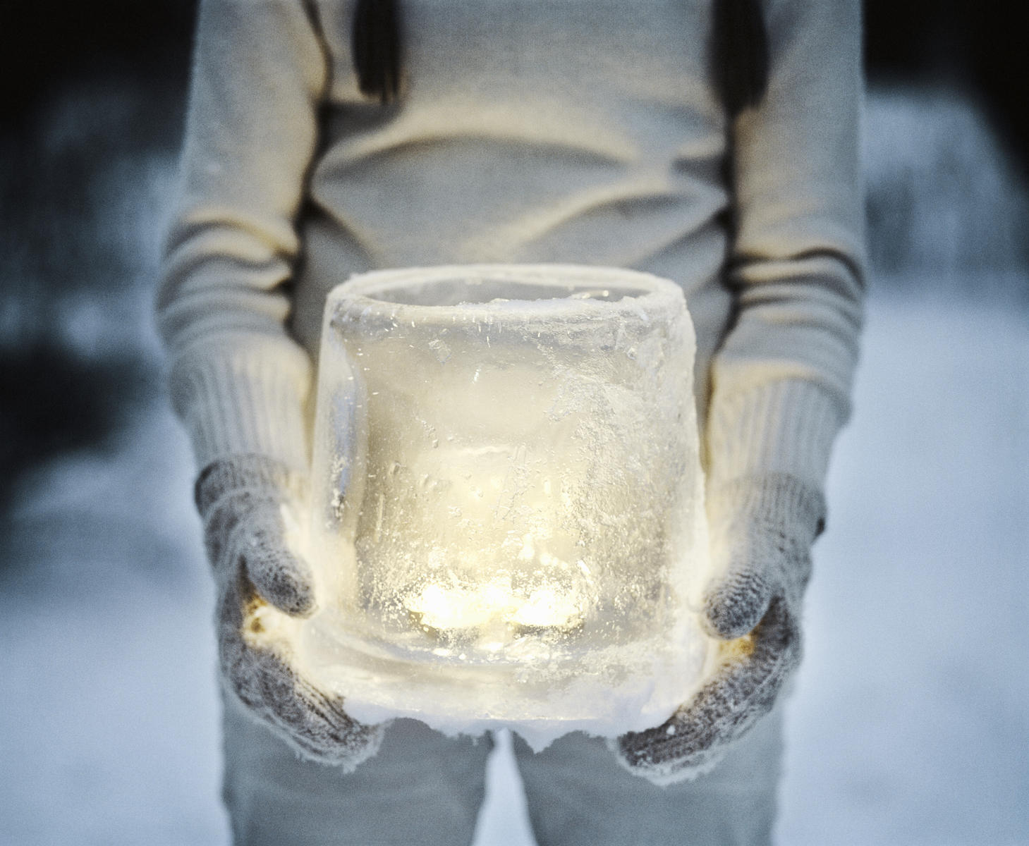woman holding an ice lantern in snow