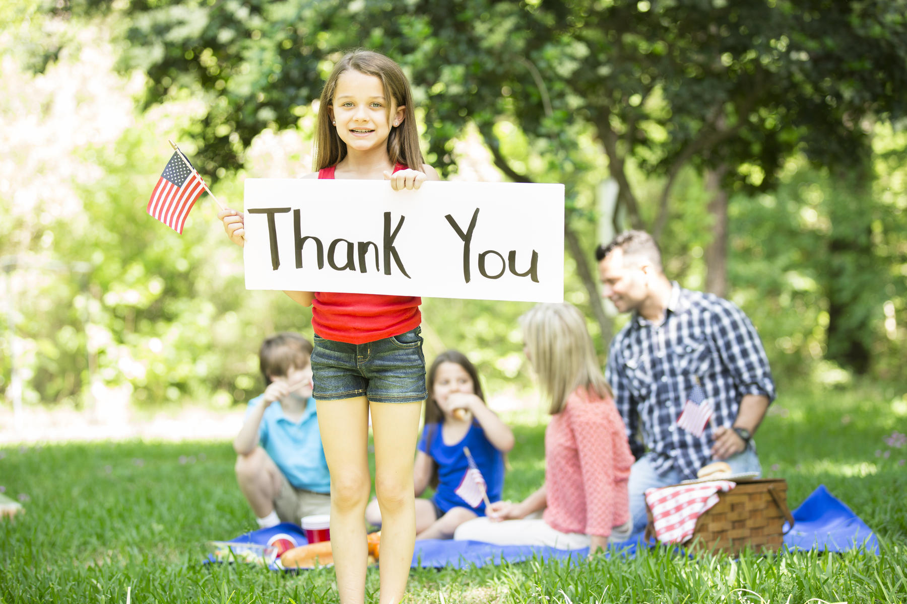 Child holds 'Thank You' sign with American flag for Memorial Day