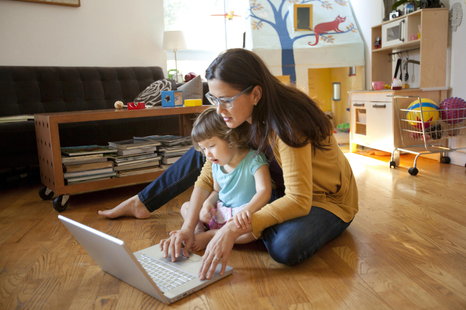 Mother and daughter using laptop in living room