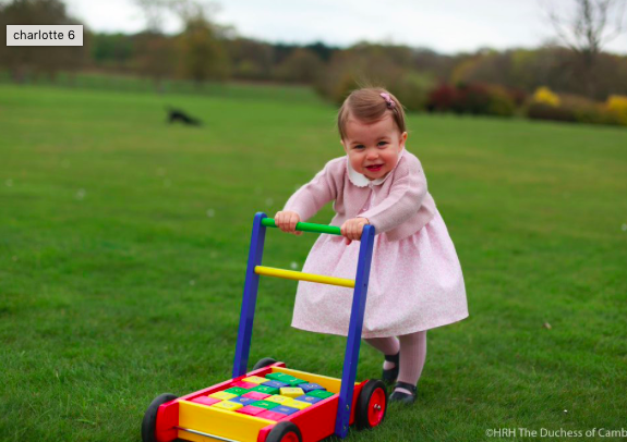 Princess Charlotte with toy lawn mower on palace lawn