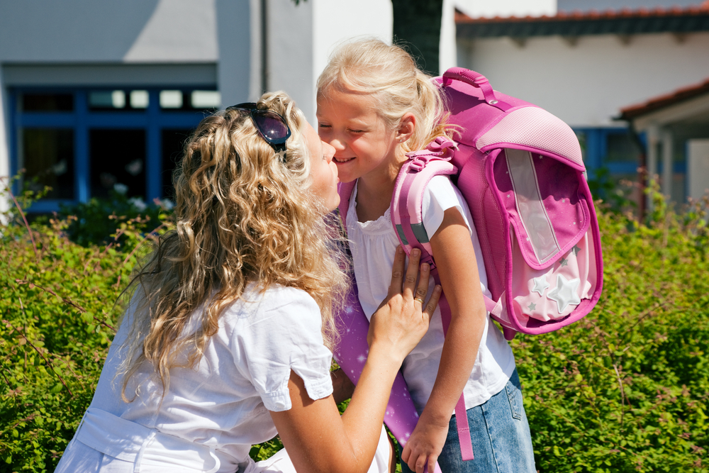 mom kissing daughter goodbye at school