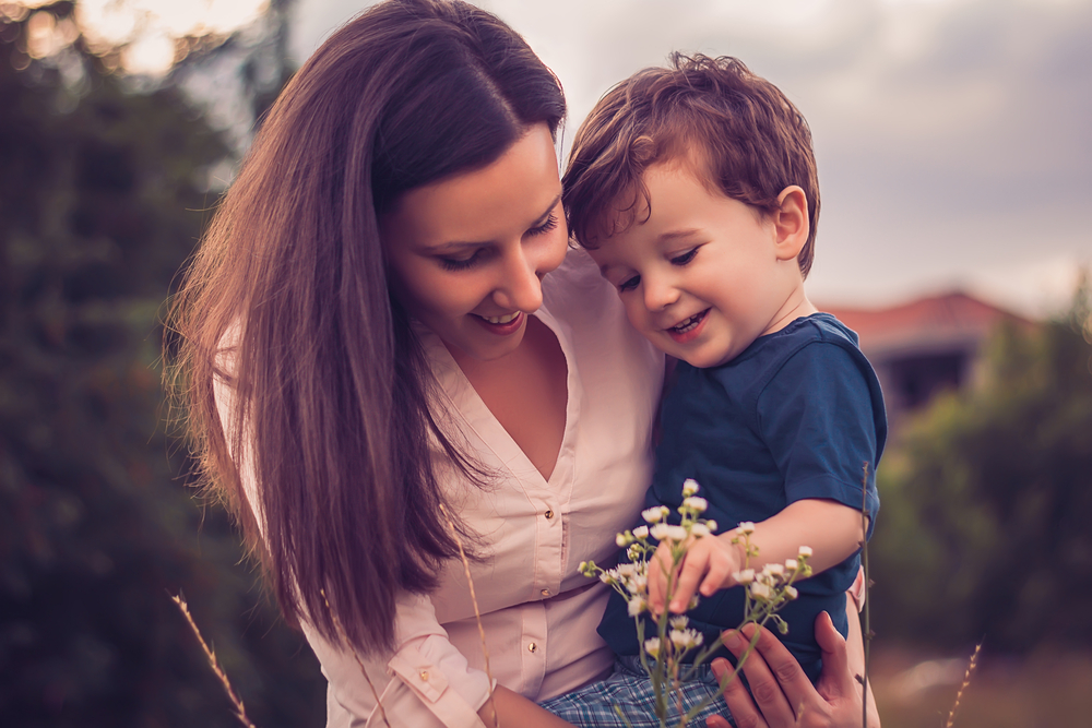 Caring Toddler Mother Son Look At Flowers
