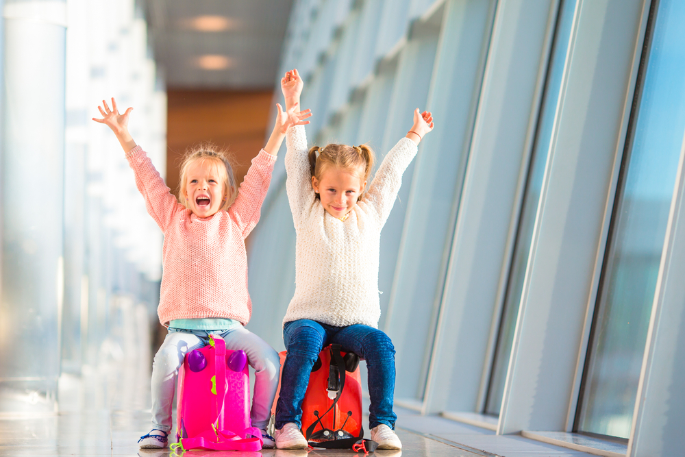Flying With Kids Two Girls Arms Up At Airport