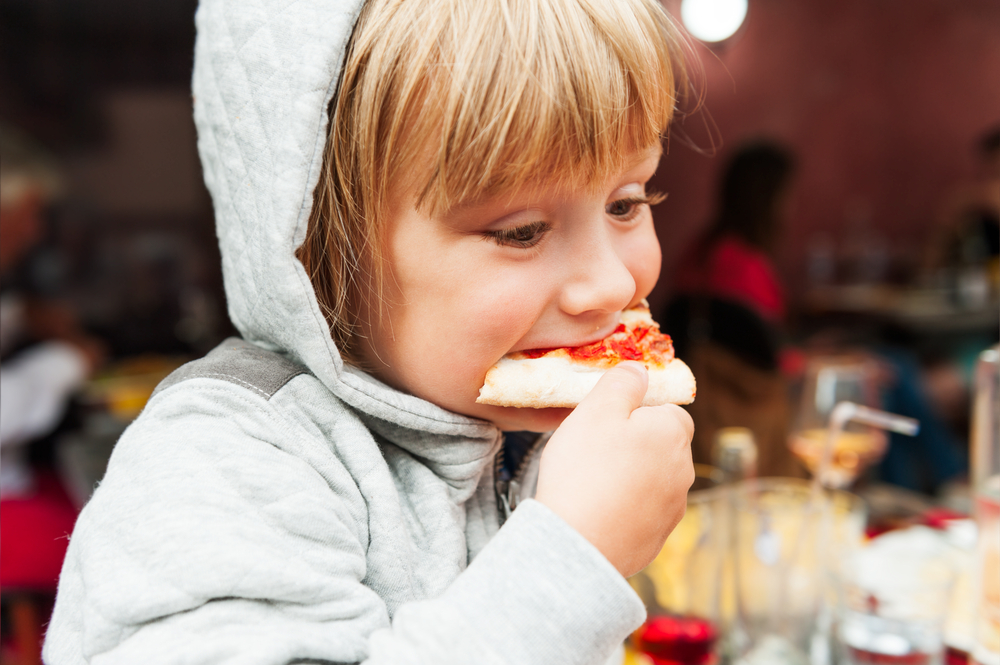 Sensory Friendly Businesses Young Boy In Hoodie Eats Pizza