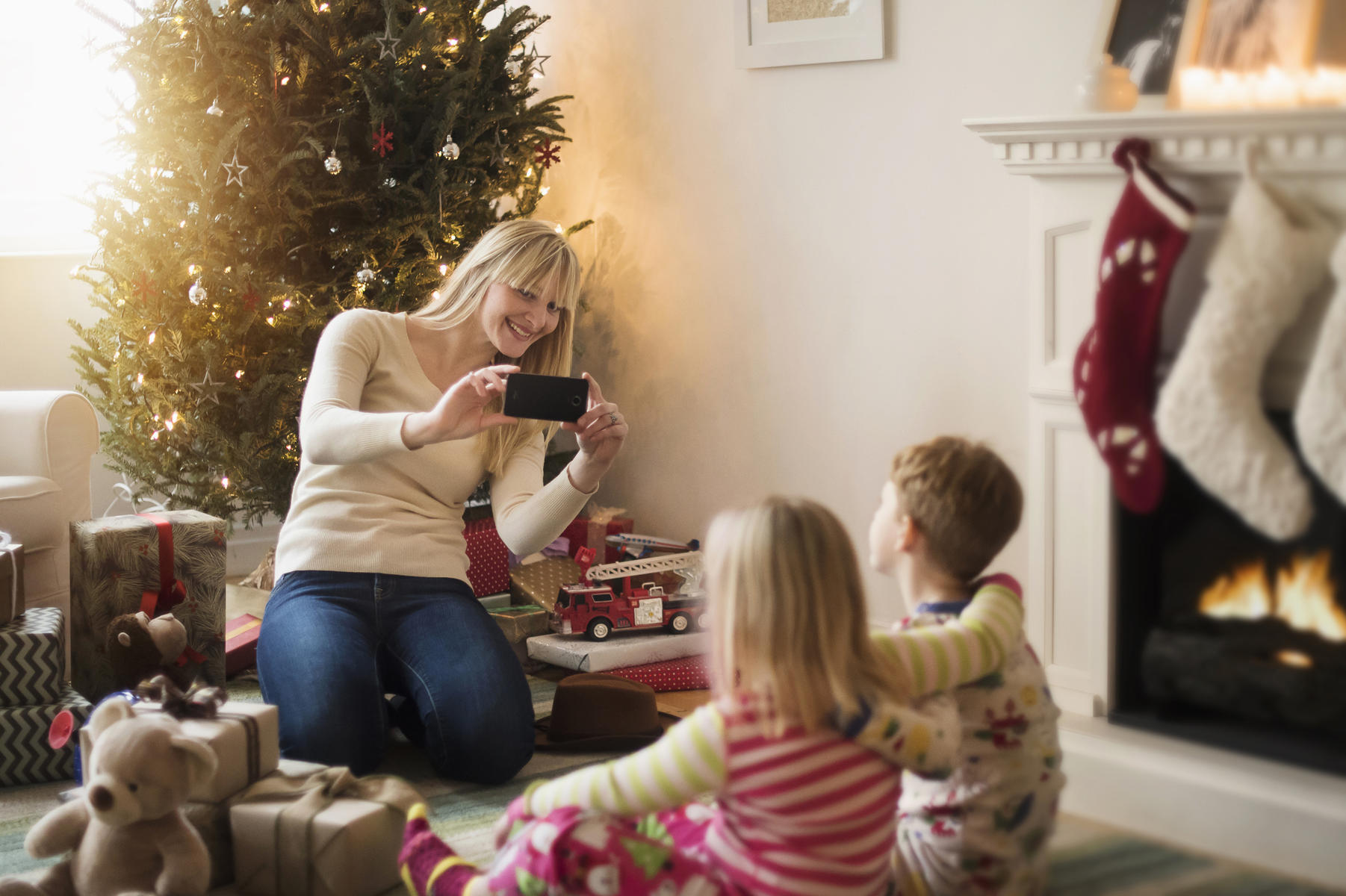 Mother with children opening Christmas presents and taking photos