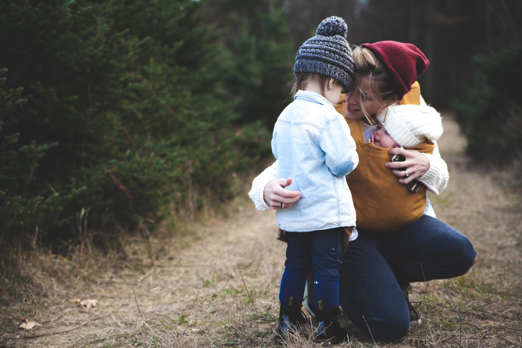 Mother Holding Baby and Talking to Other Child Outside Hike