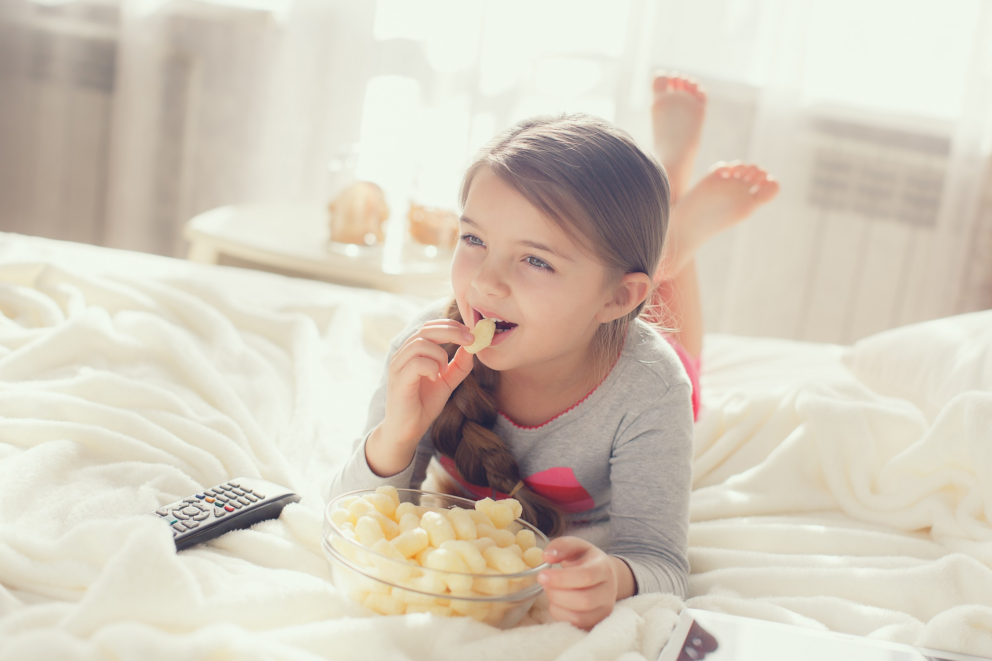 Young Girl Snacking on Cheese Puffs in Bed with TV Remote Control