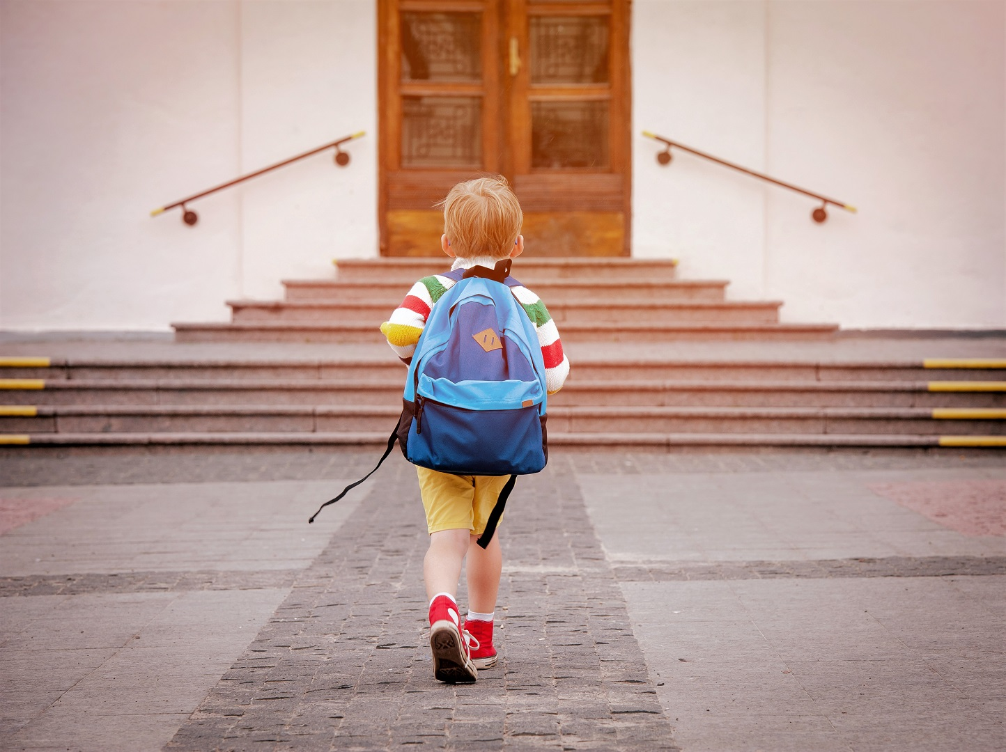 Young Boy Walking With Heavy Backpack On Back