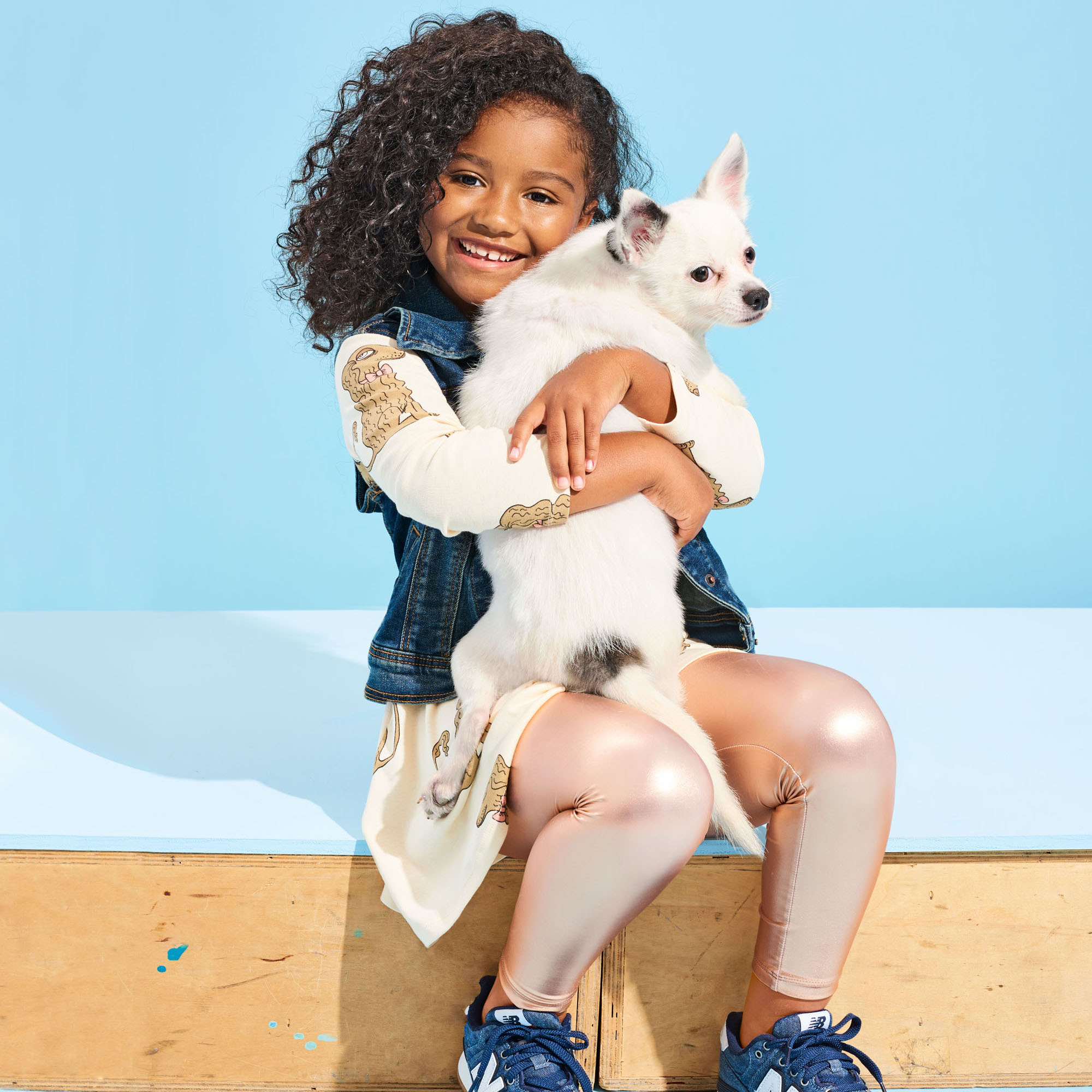 girl with curly hair sitting and holding white chihuahua