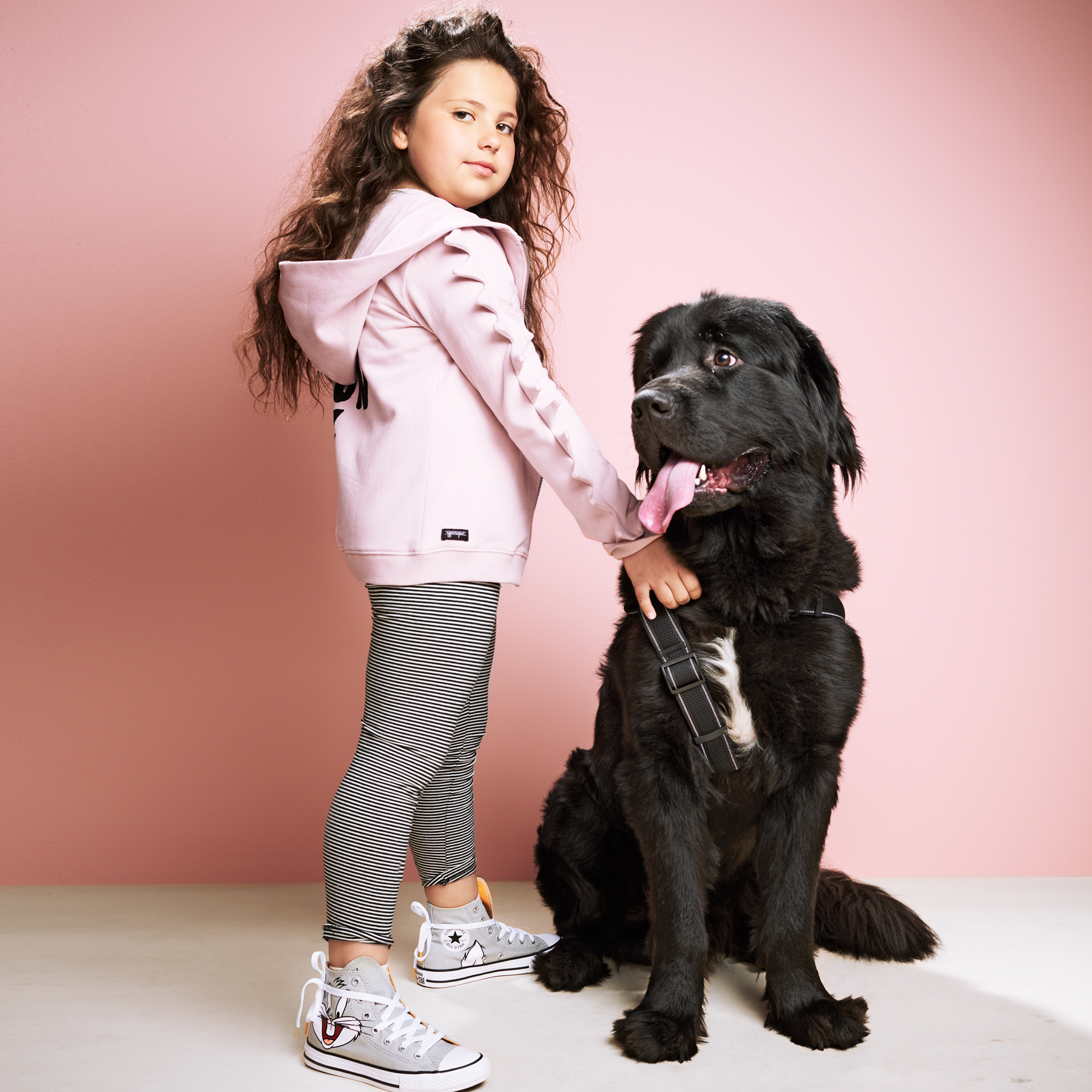 girl in pink hoodie standing with black newfoundland dog