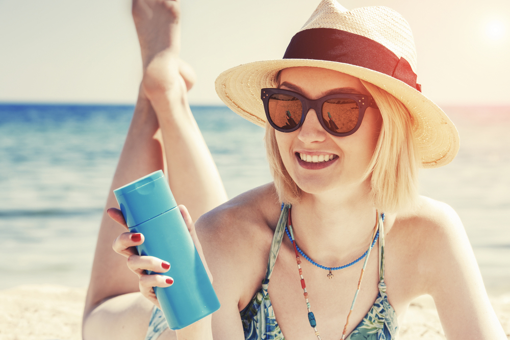 Pale woman on the beach holding sunscreen