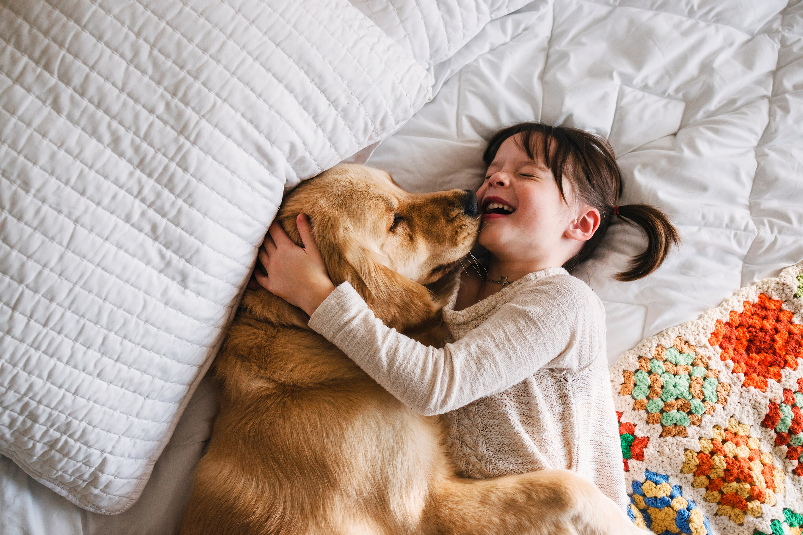 Little Girl and Dog Cuddle on Bed