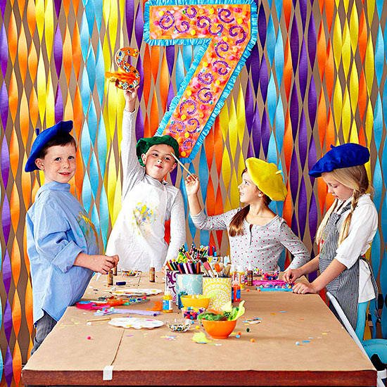 Artist kids at table with streamers behind them