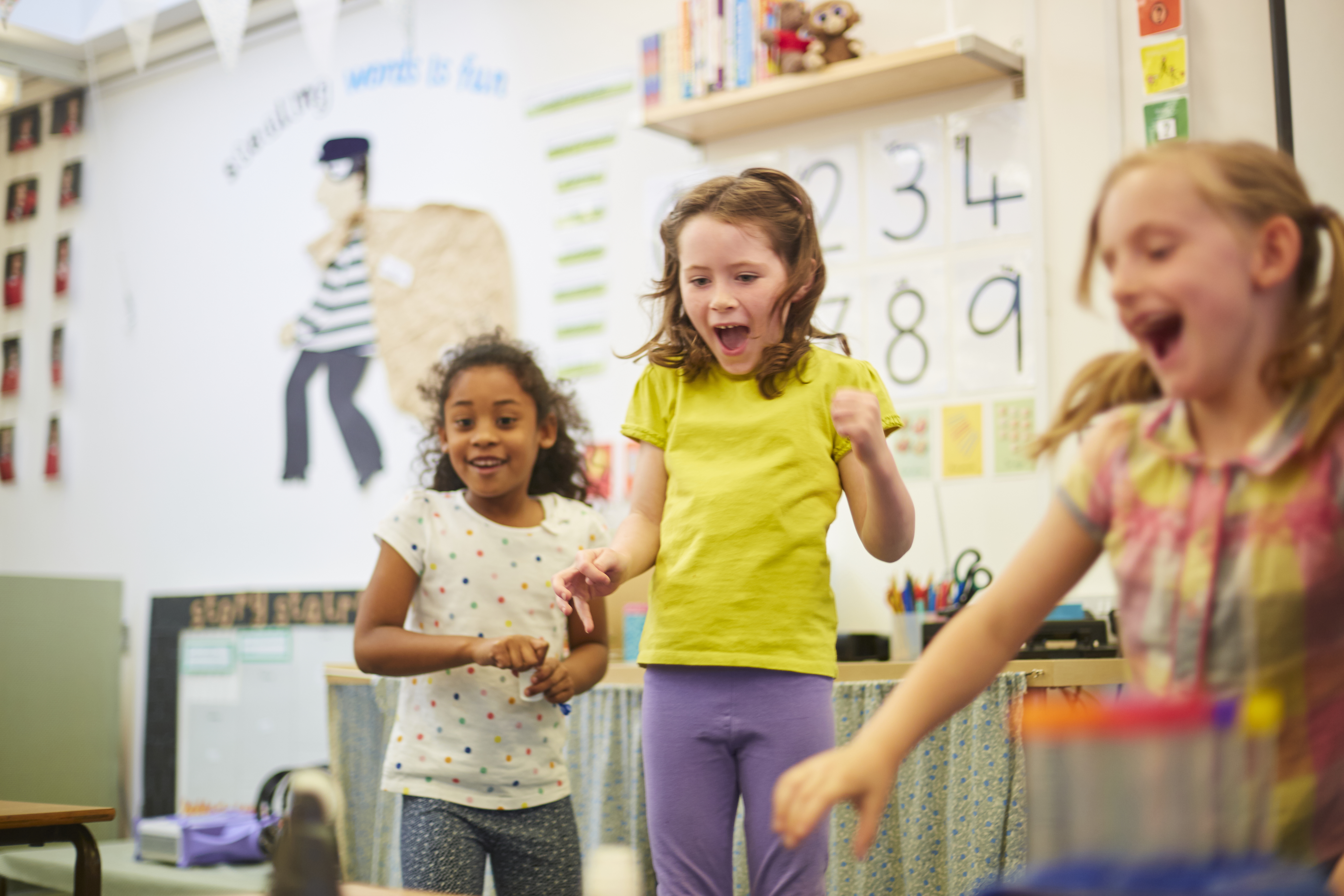 Three Girls Laughing In Elementary School Classroom