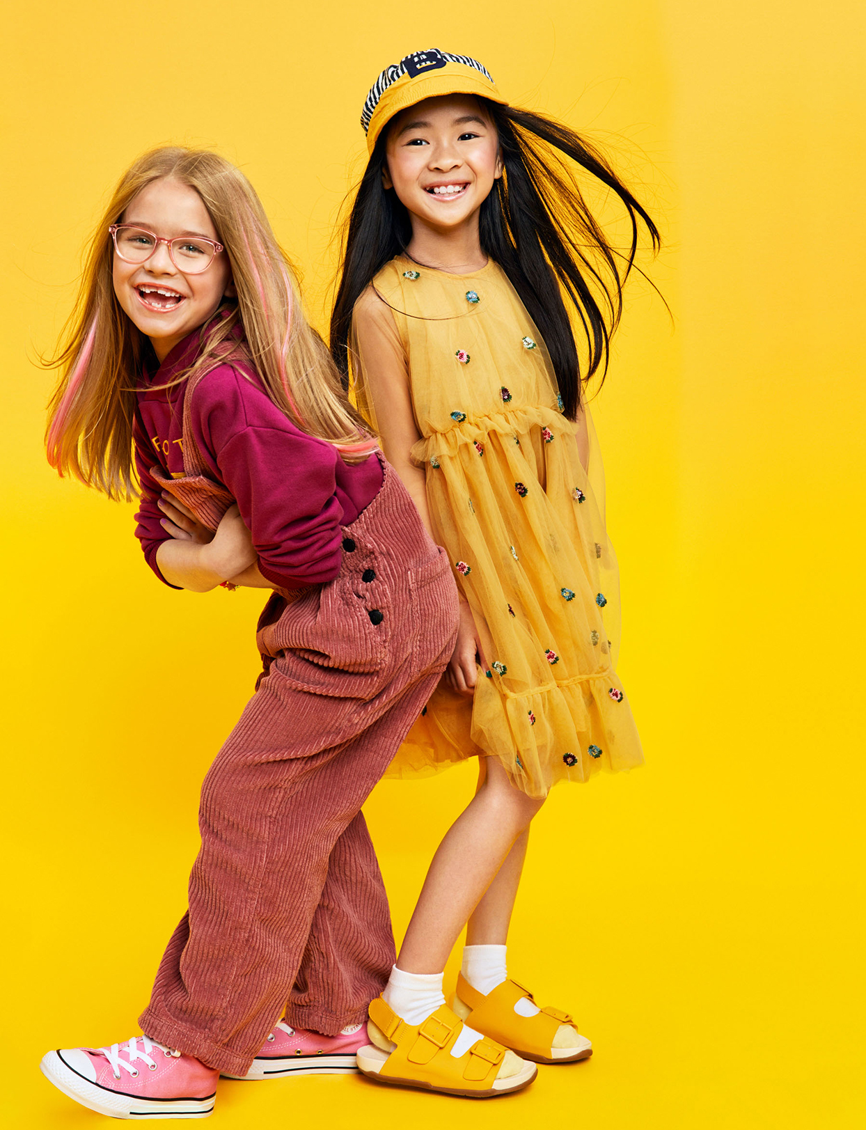 two girls back to back smiling on yellow background