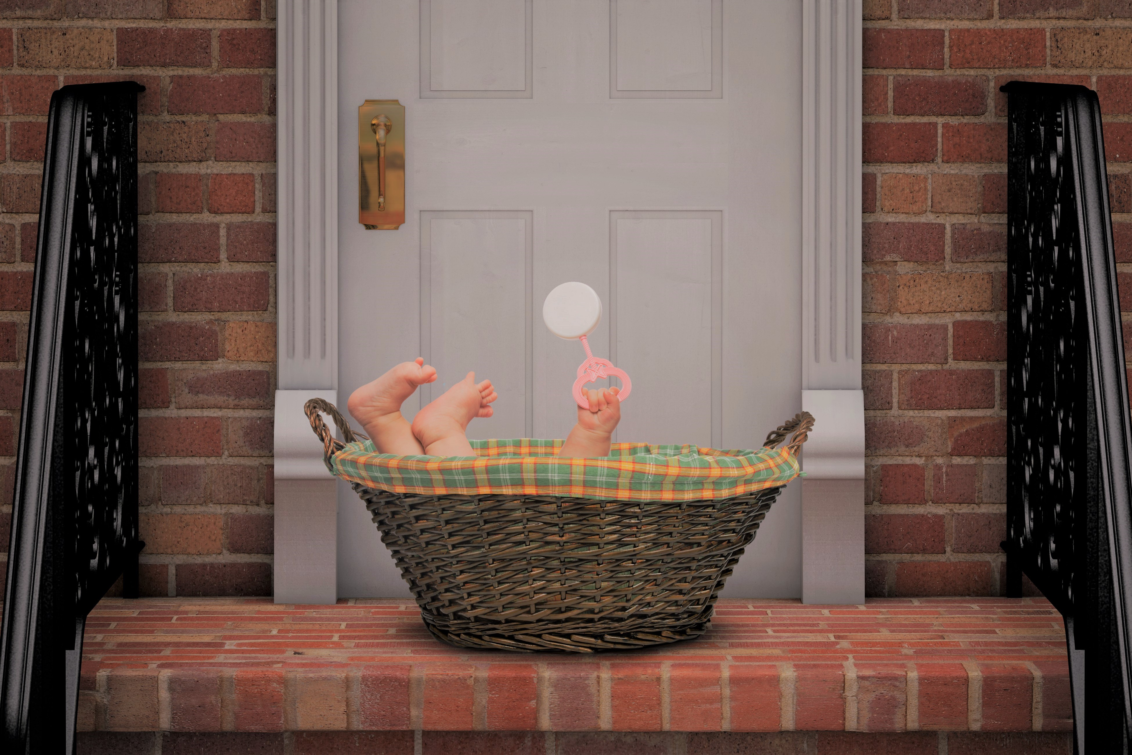 Baby Holding Pink Rattle In Basket on Doorstep