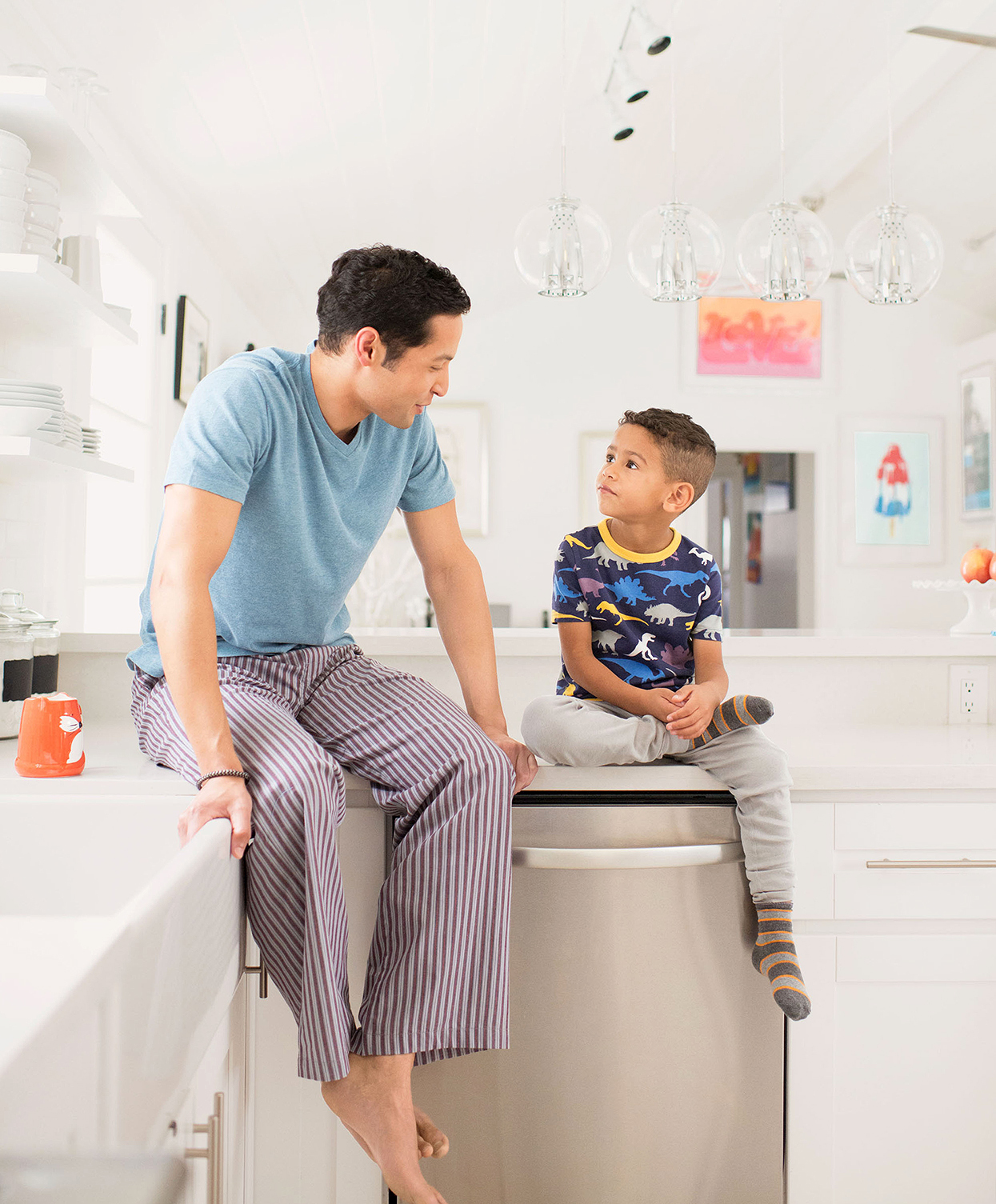 father and son in pajamas on kitchen countertop talking
