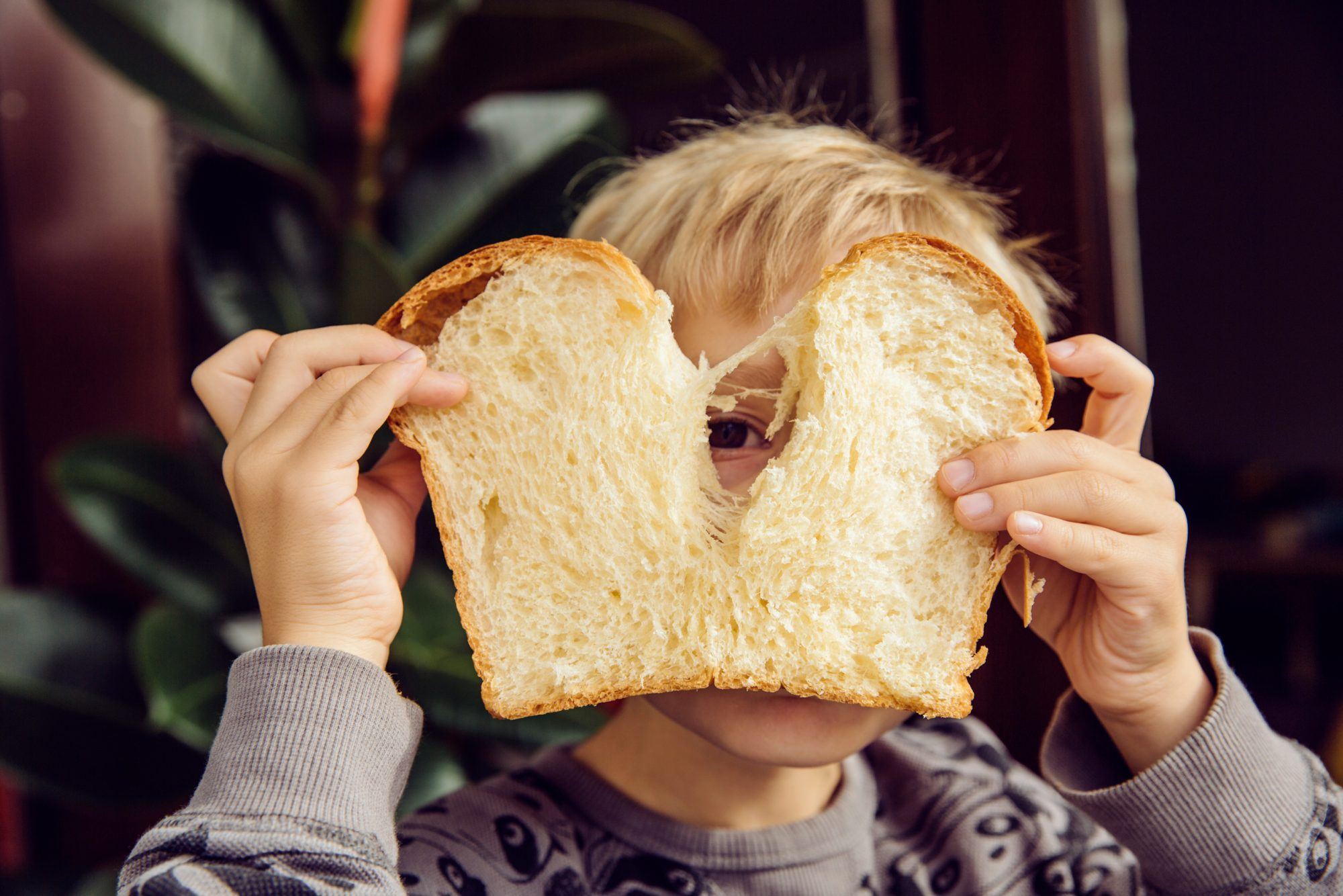 child holding up slice of bread