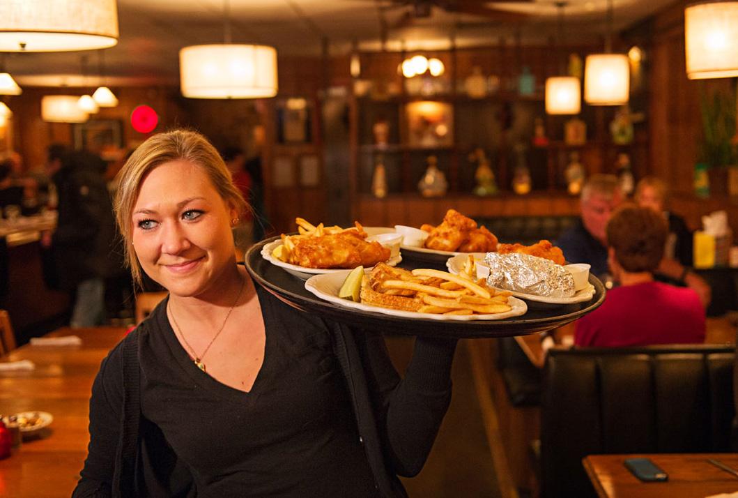 A waitress serves platters of fish at Avenue Bar.