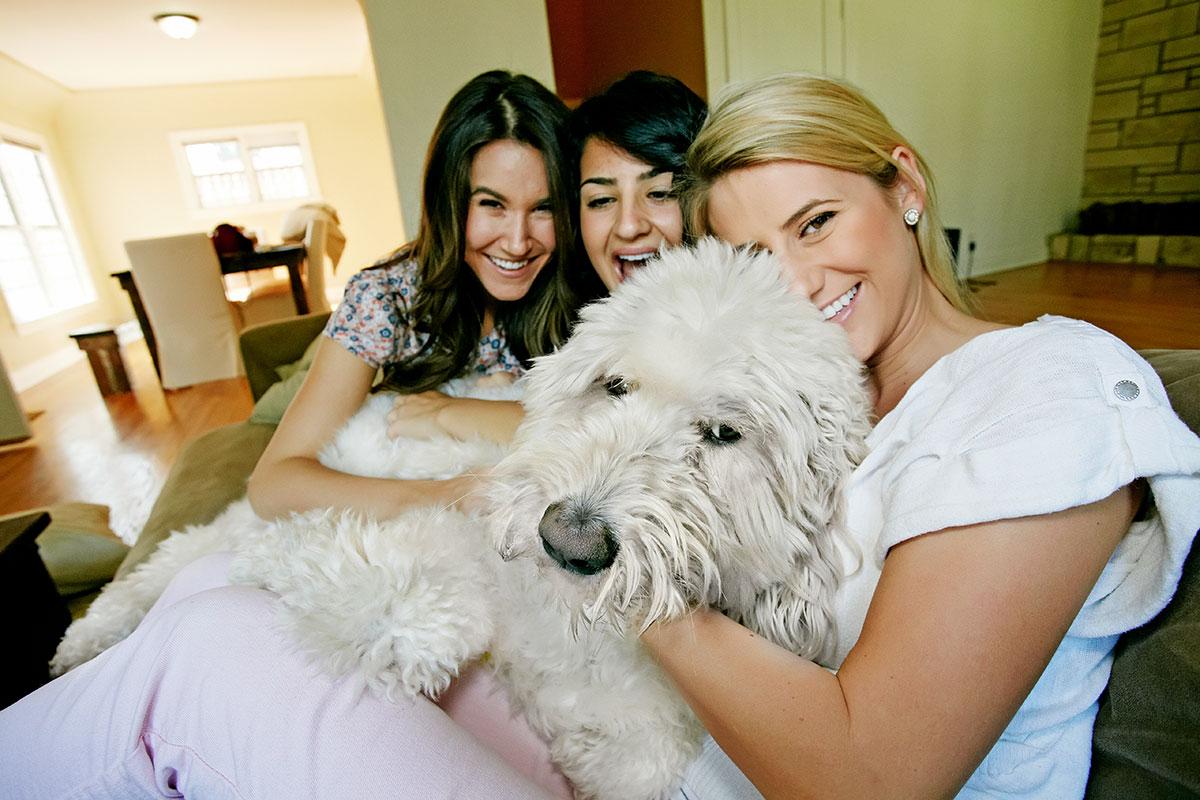 women petting dog on sofa