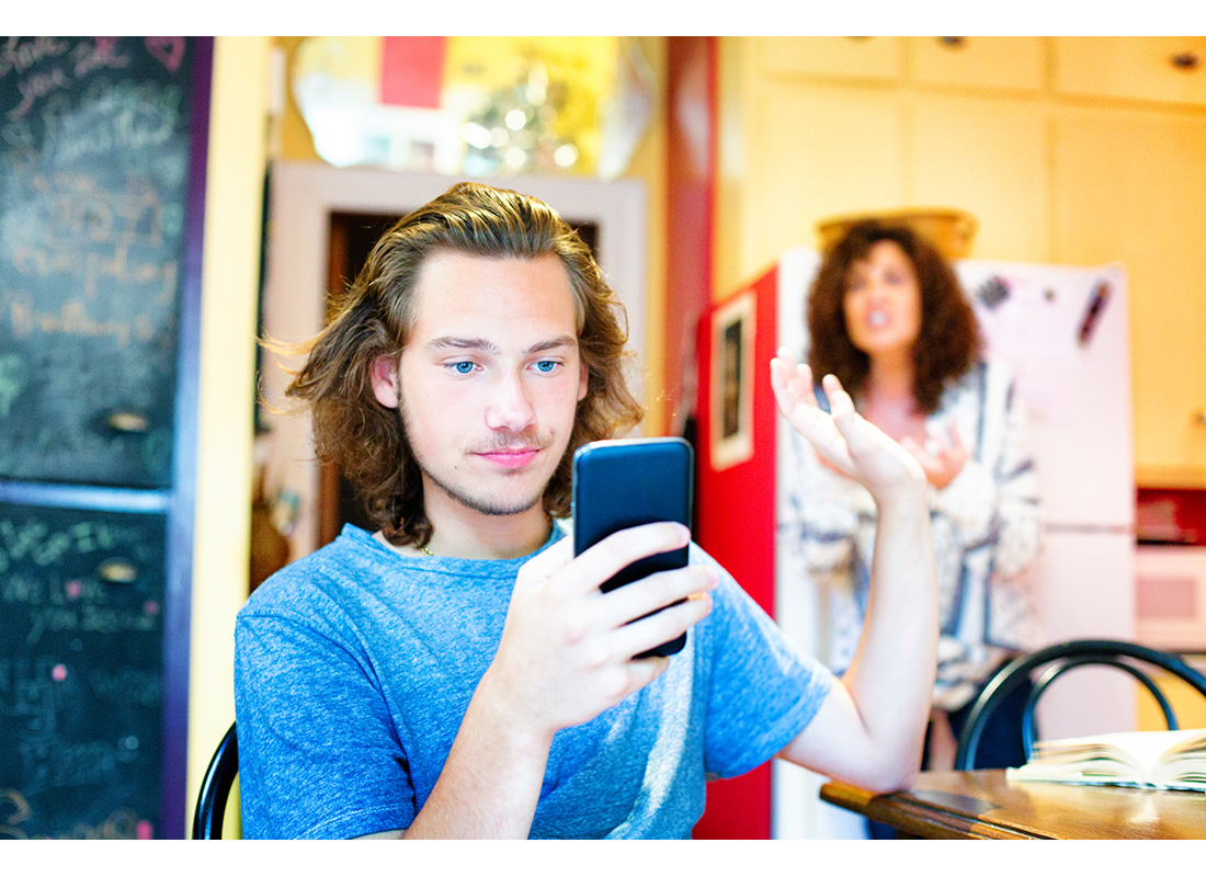 Male teenager ignoring scolding mom with mobile phone