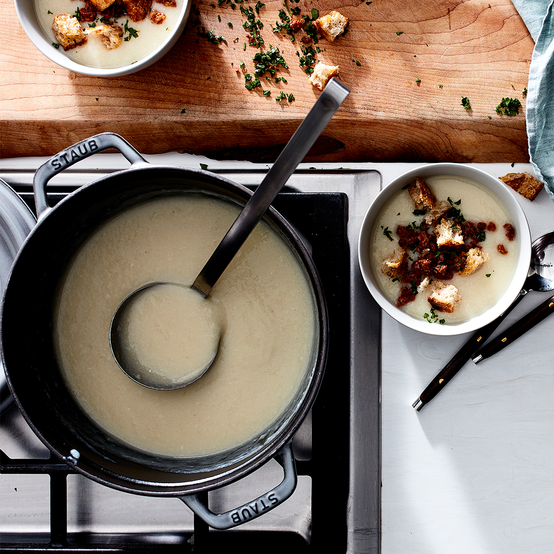 Creamy Cauliflower Soup with Chorizo in stove pot with ladle
