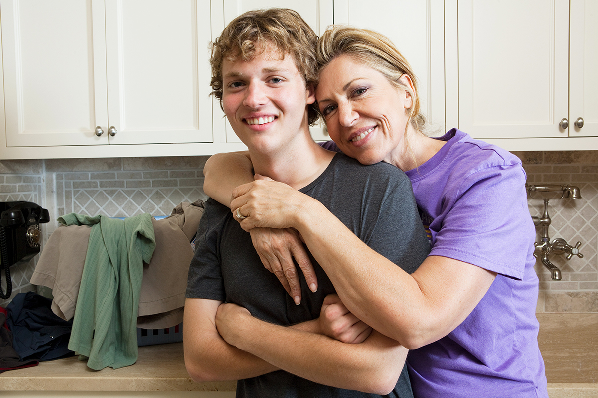 portrait of mother and teen son in laundry room