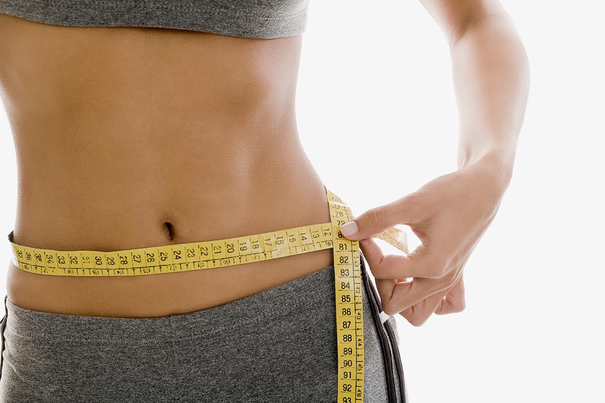 fit woman measuring waist