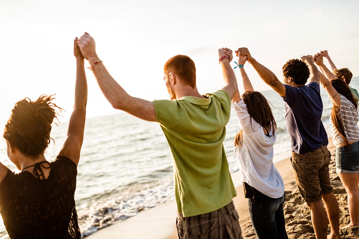teen volunteers with arms raised on beach