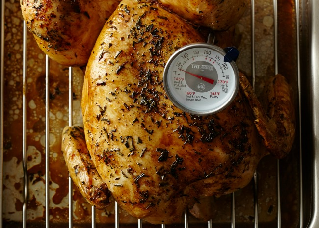 checking the chicken readiness with a thermometer