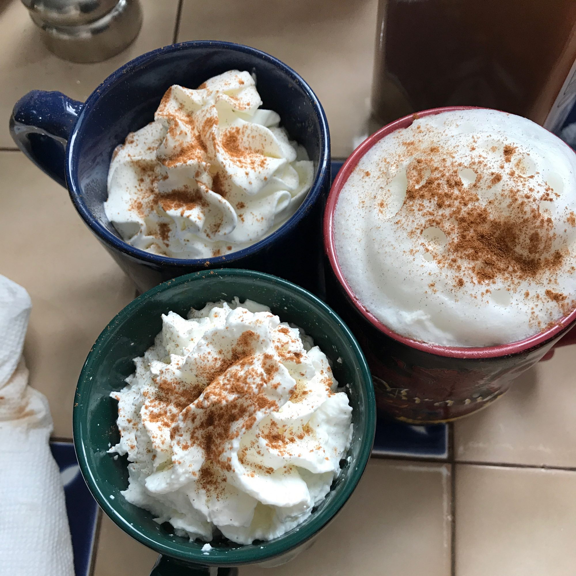 three cups of foamy hot chocolate