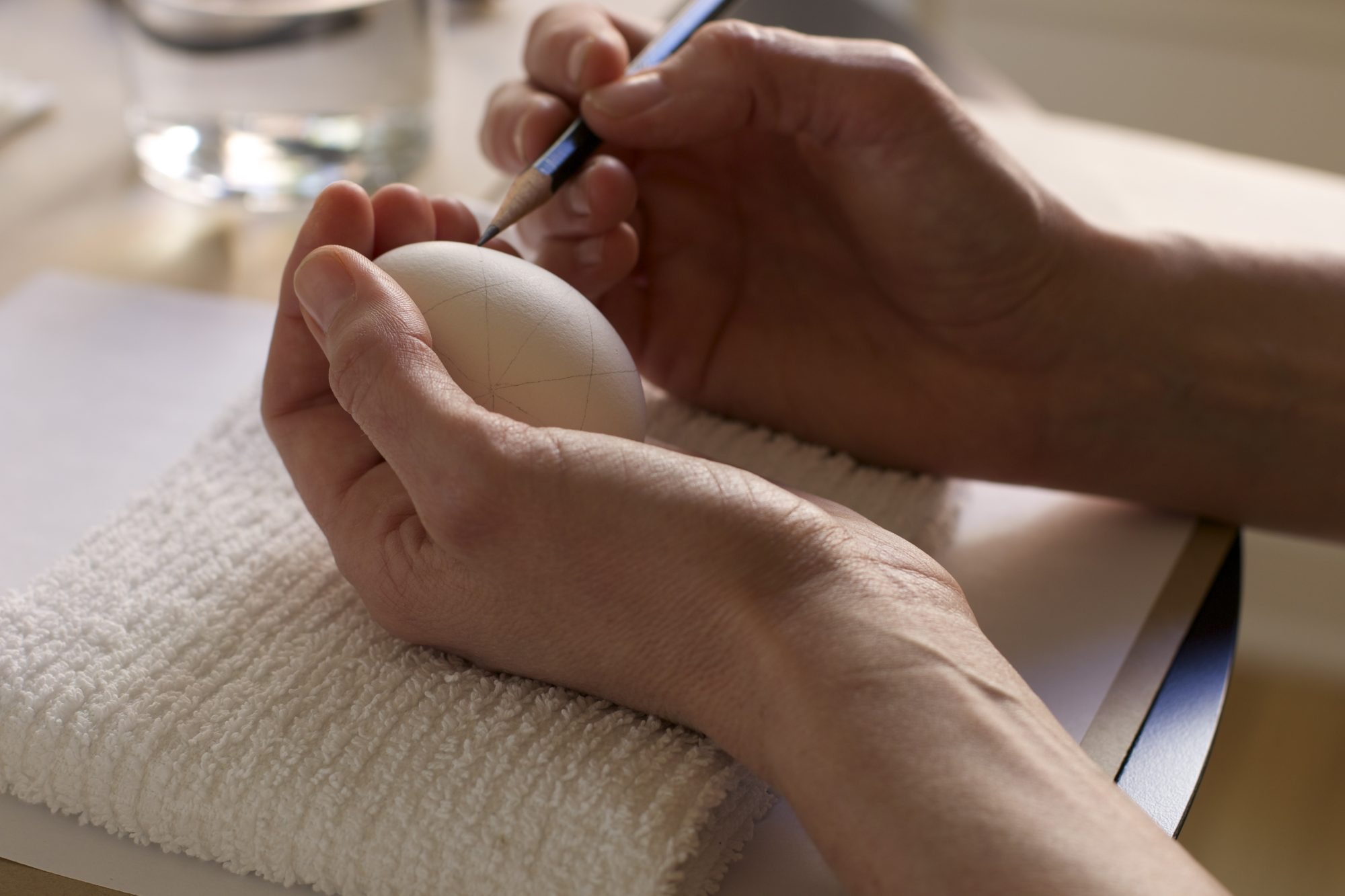 Drawing patterns on a white egg with a pencil