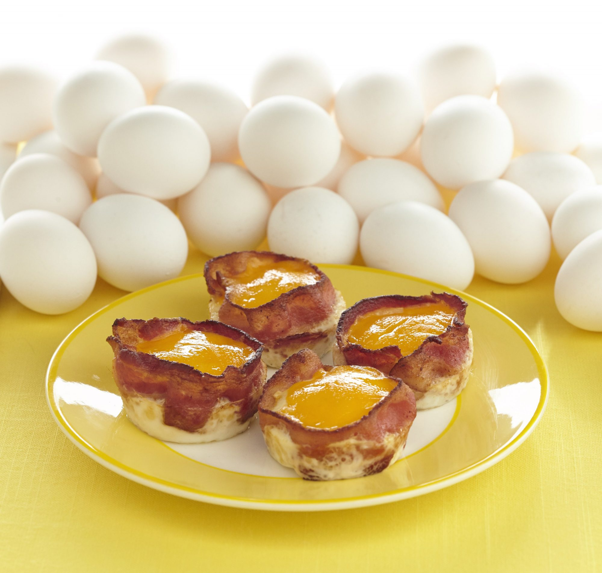 Egg and bacon cups with white eggs behind